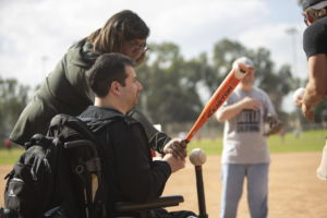 Film crew captures a man in wheelchair being guided through the process of hitting a baseball off a batting tee.