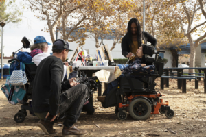 Film crew capturing participant sitting in a wheelchair and sipping from a cup with a straw while on a break from painting on a canvas propped up on a picnic bench.