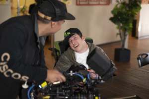 Camera person filming smiling participant sitting in wheelchair at table