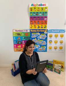 CDS Educator Misbah Saad on floor with ipad