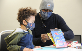 Kid and adult working on a sticker project while wearing masks