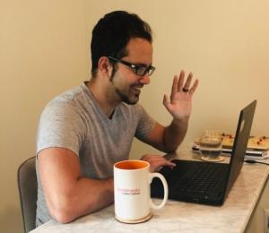 Michael Dreyfuss waving to client via laptop webcam.