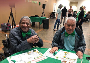 Seniors sitting at table with St. Patrick's Day decorations