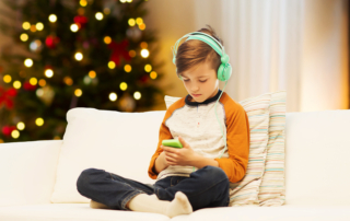 boy with smartphone and headphones listening to music or playing game at home over christmas tree lights background