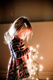 Young girl looks at a strand of Christmas lights